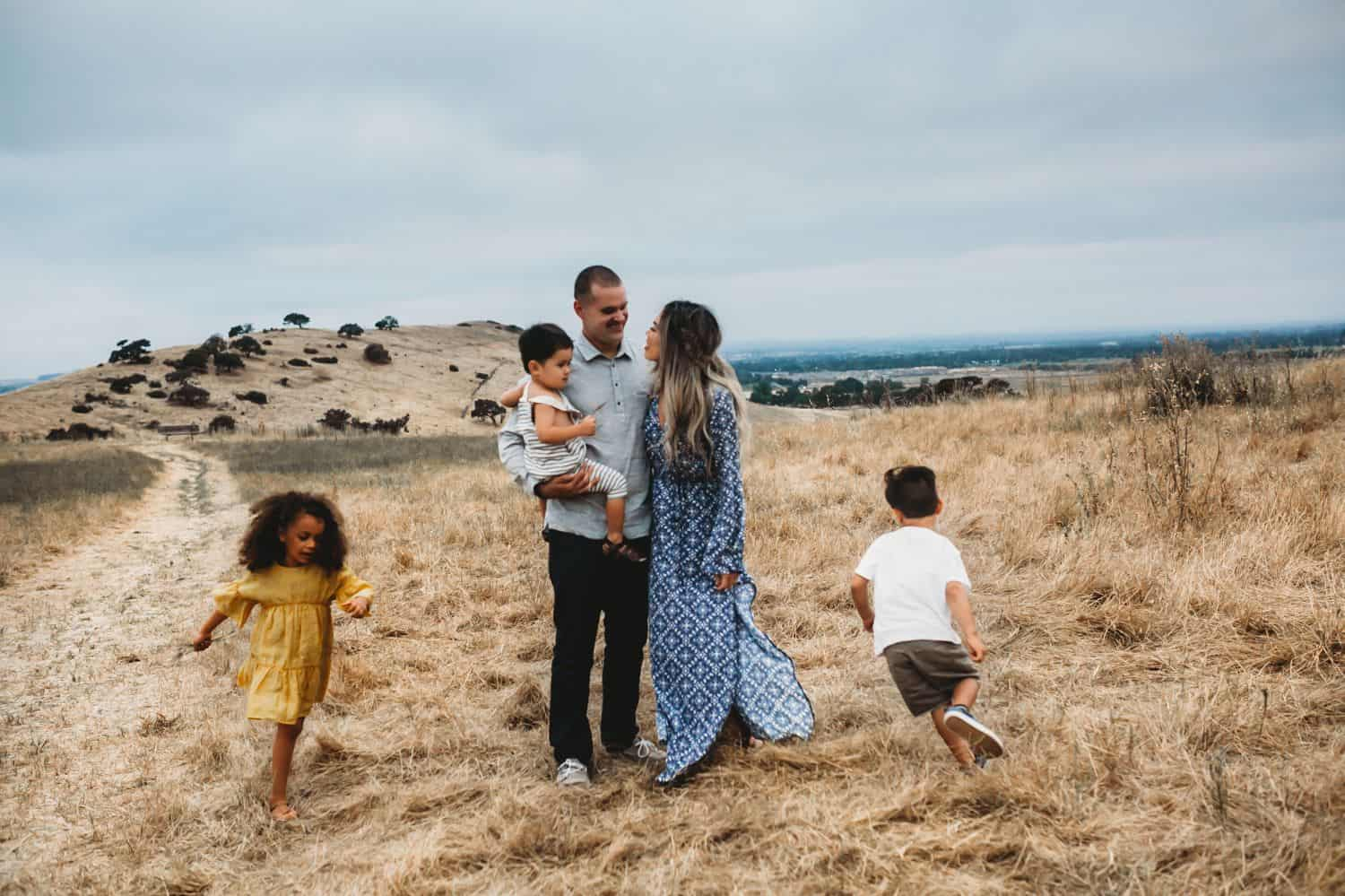Two parents stand in a field holding their toddler while two older children run circles around them.