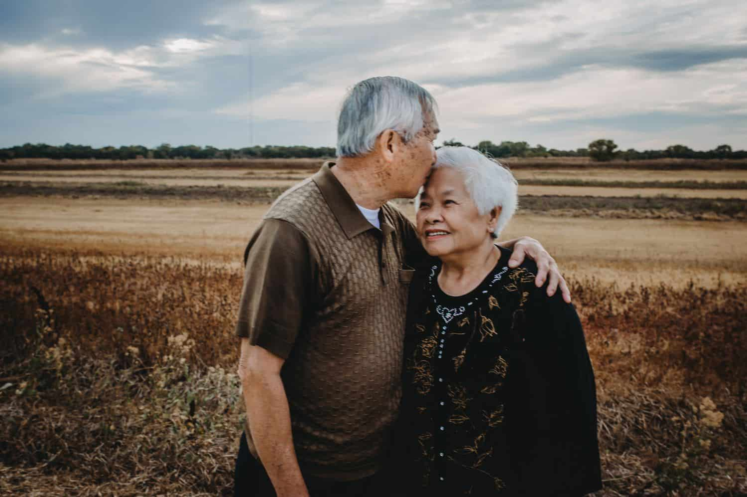 A grandfather kisses his wife on the forehead while standing in a field.