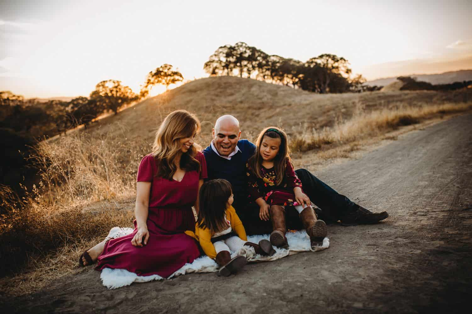Two parents and their two young daughter sit on a picnic blanket in the middle of a field at sunset.