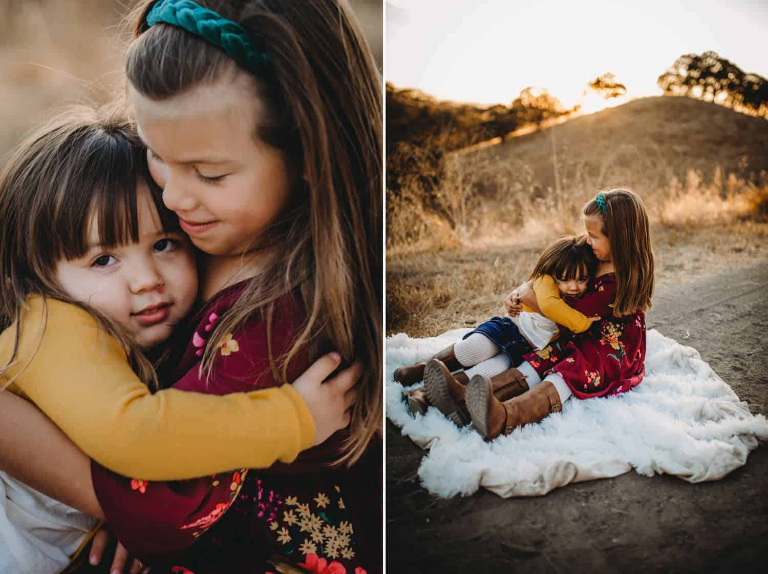 Two sisters hug while sitting on a furry blanket in the middle of a field at sunset.