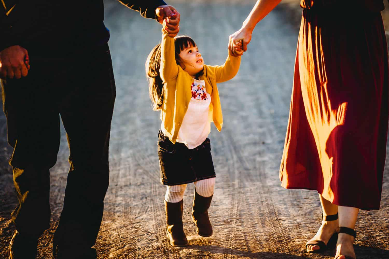 A little girl holds her parents hands and skips down a gravel road. The parents are only visible from the waist-down.