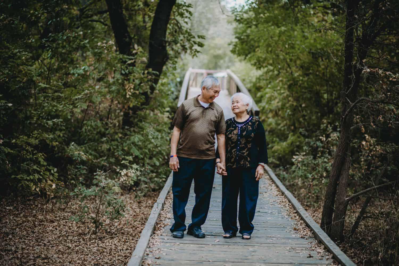 An elderly couple walks hand-in-hand down a forest boardwalk.