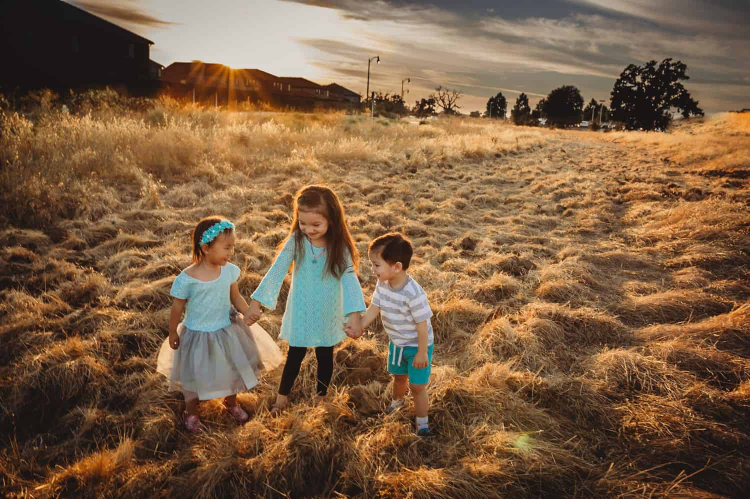 A young girl holds her younger siblings' hands as they walk through a field at sunset.