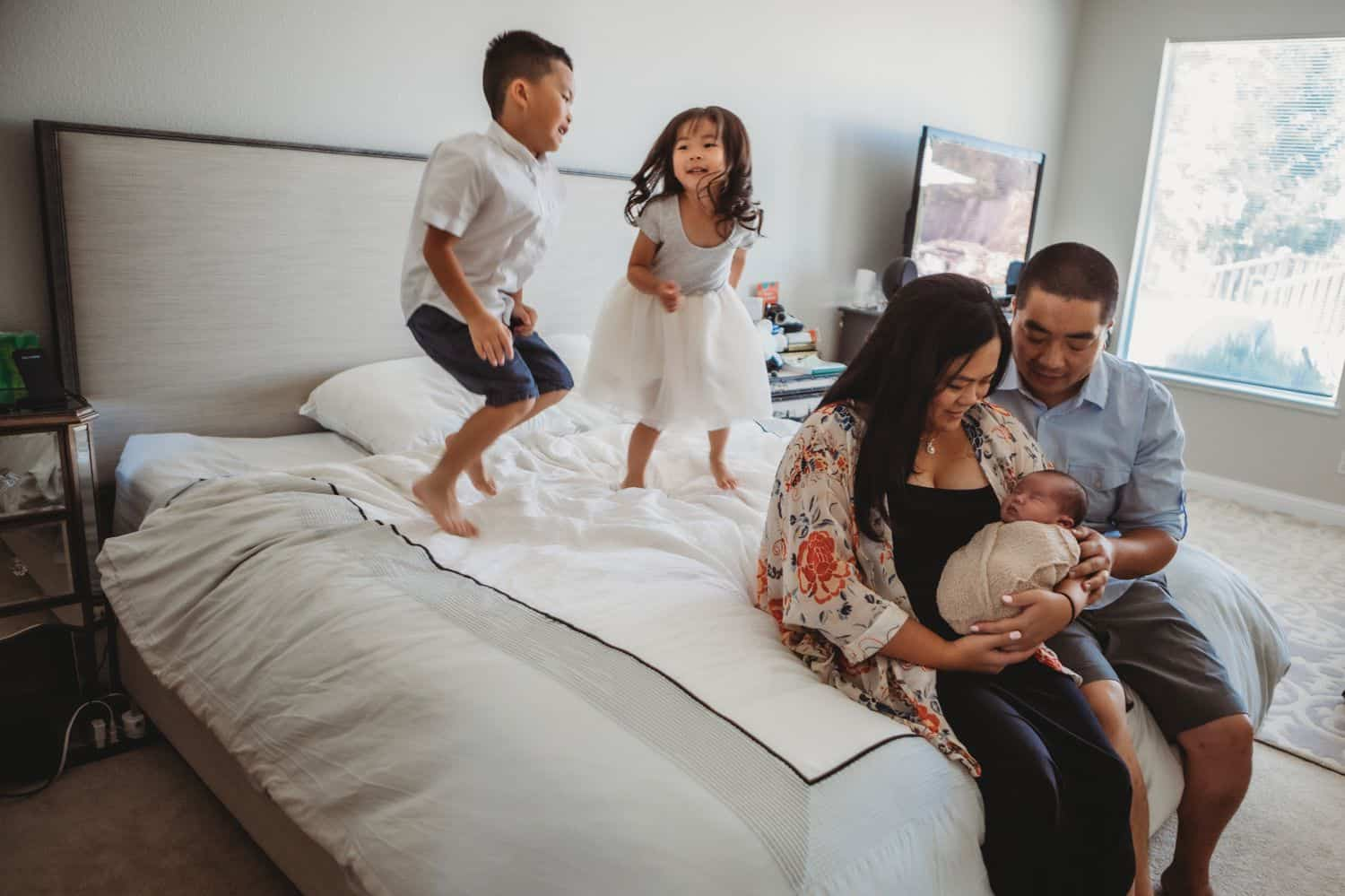 New parents sit on the edge of their bed holding their newborn baby while their young son and daughter jump on the bed behind them.