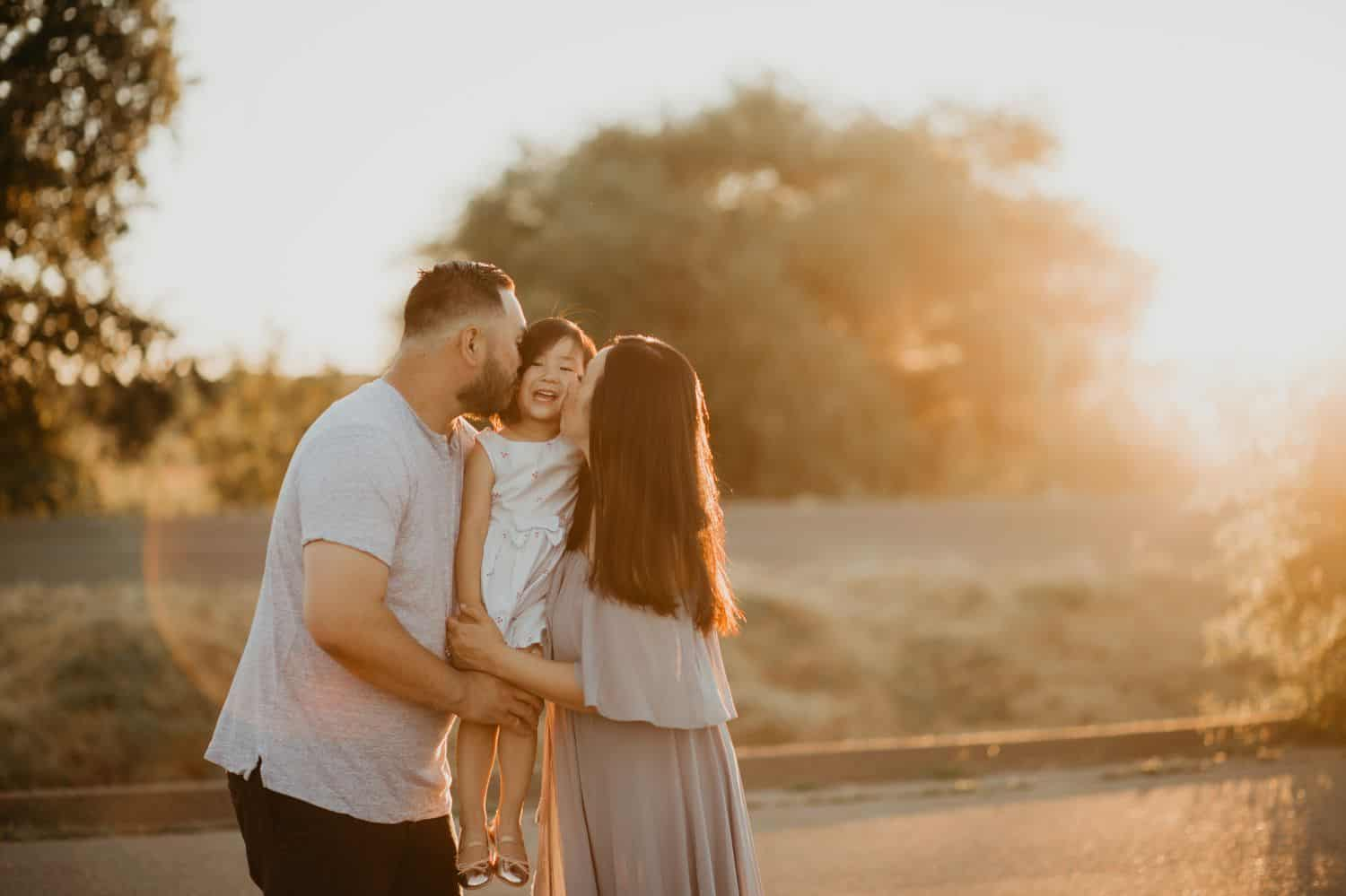 Two parents stand in a circle of sun flare. They're holding their young daughter between them and kissing her on both cheeks.