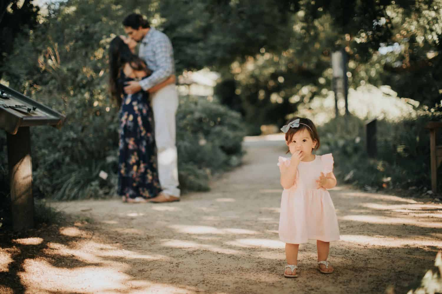 Two parents kiss in the background. In the foreground, their toddler daughter stands in a pink dress looking solemnly at the camera.