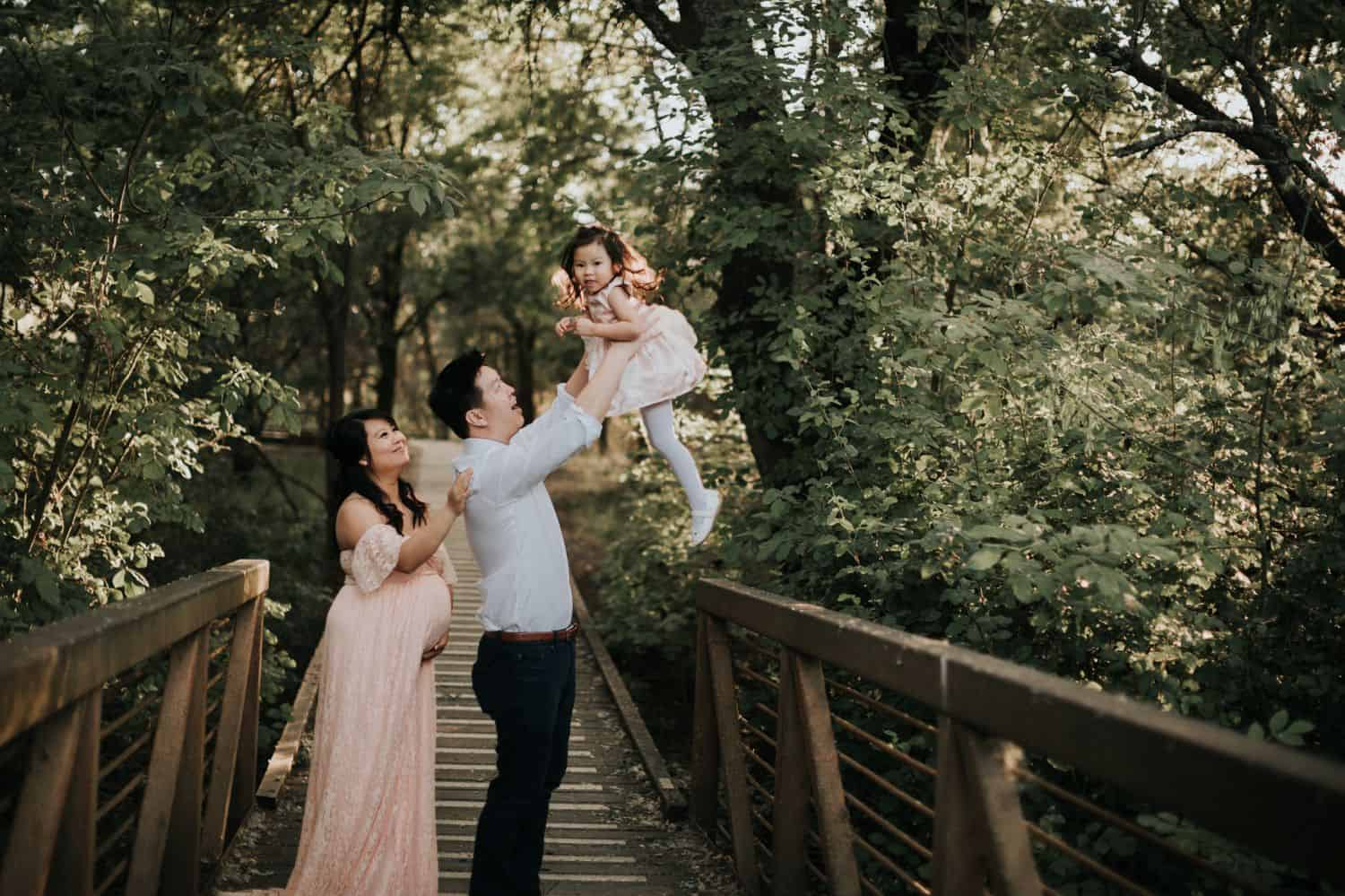 A pregnant mother stands behind her husband on a forest boardwalk. The father is holding his toddler daughter up in the air and laughing.