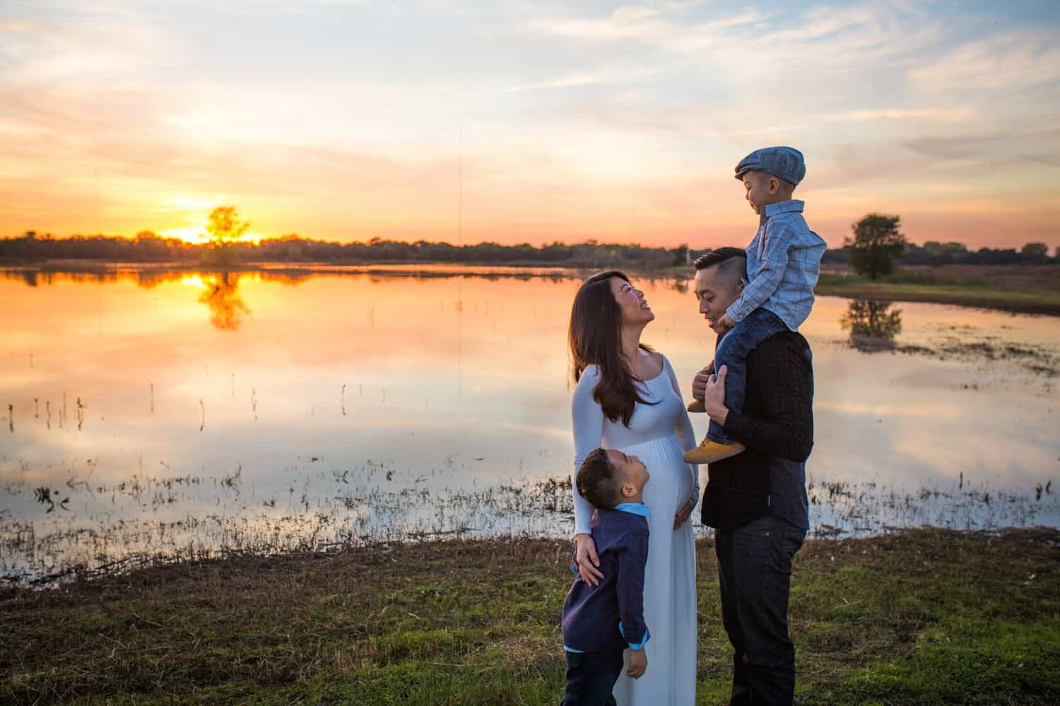 A pregnant mother and her husband stand with their two young sons beside a pond at sunset.