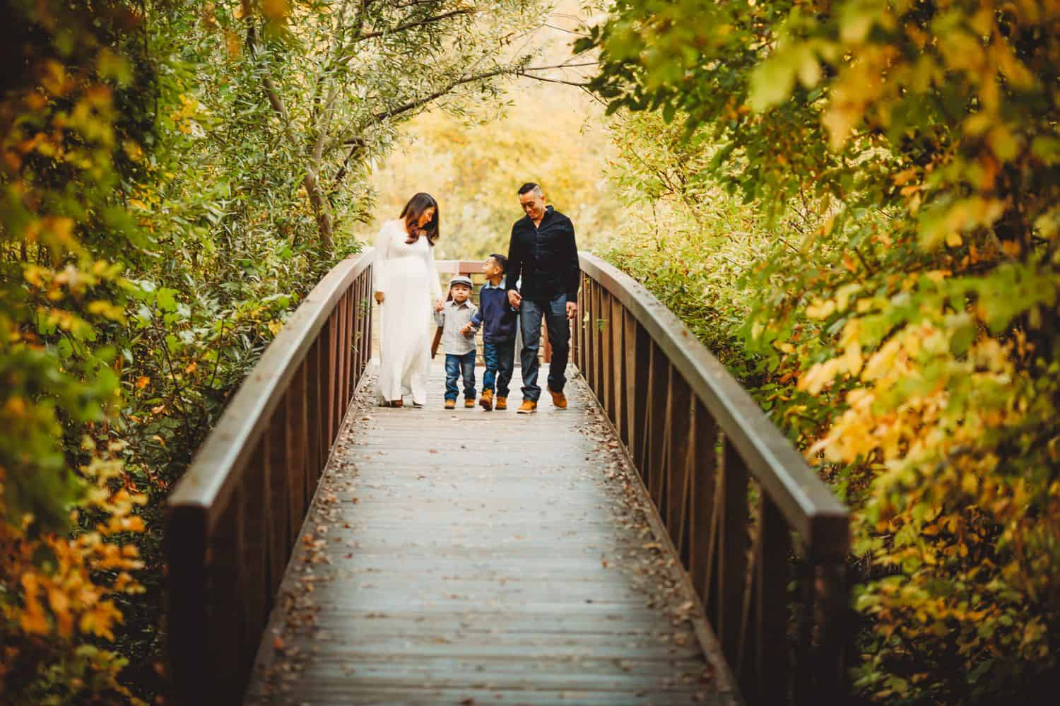 A pregnant mother in a flowing white dress walks down a forest boardwalk with her husband and two young sons. They are surrounded by fall colors.