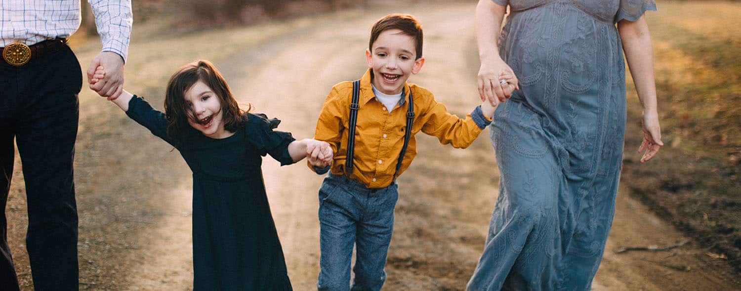 Two siblings skip down a dirt road, holding hands with their parents.