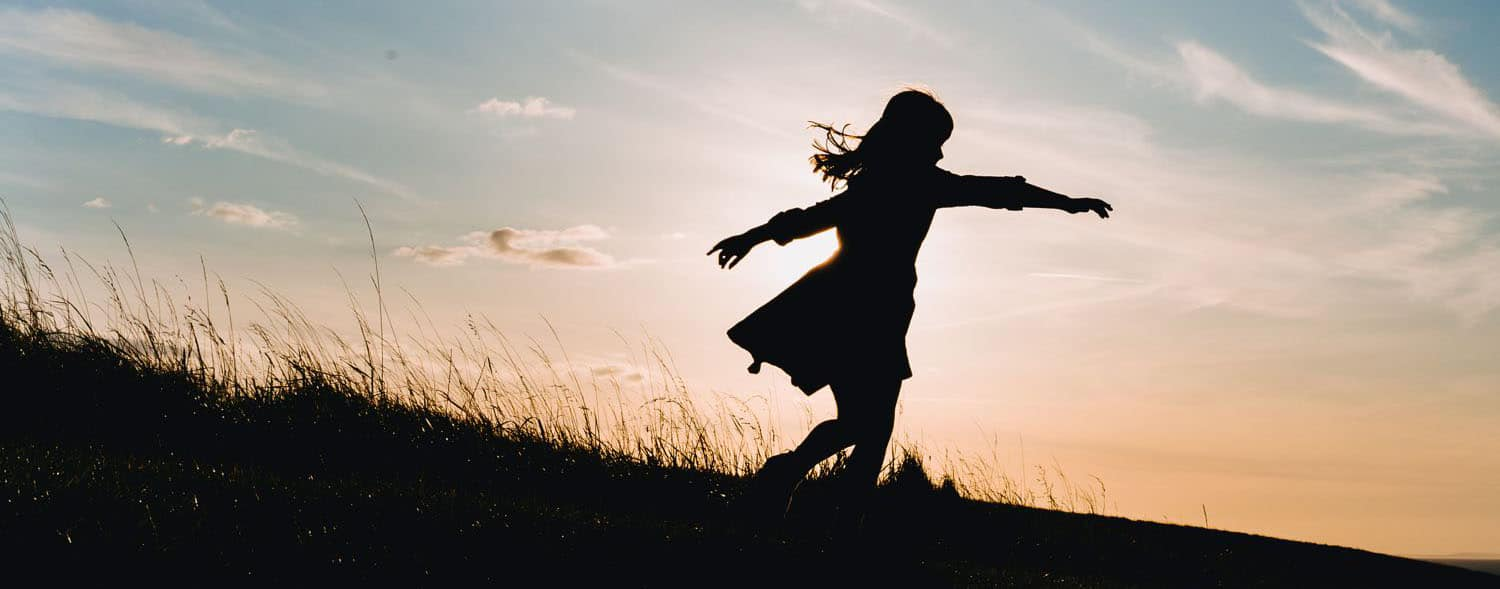 Silhouette of a child spinning in a twirly dress on a hill against the sunset.