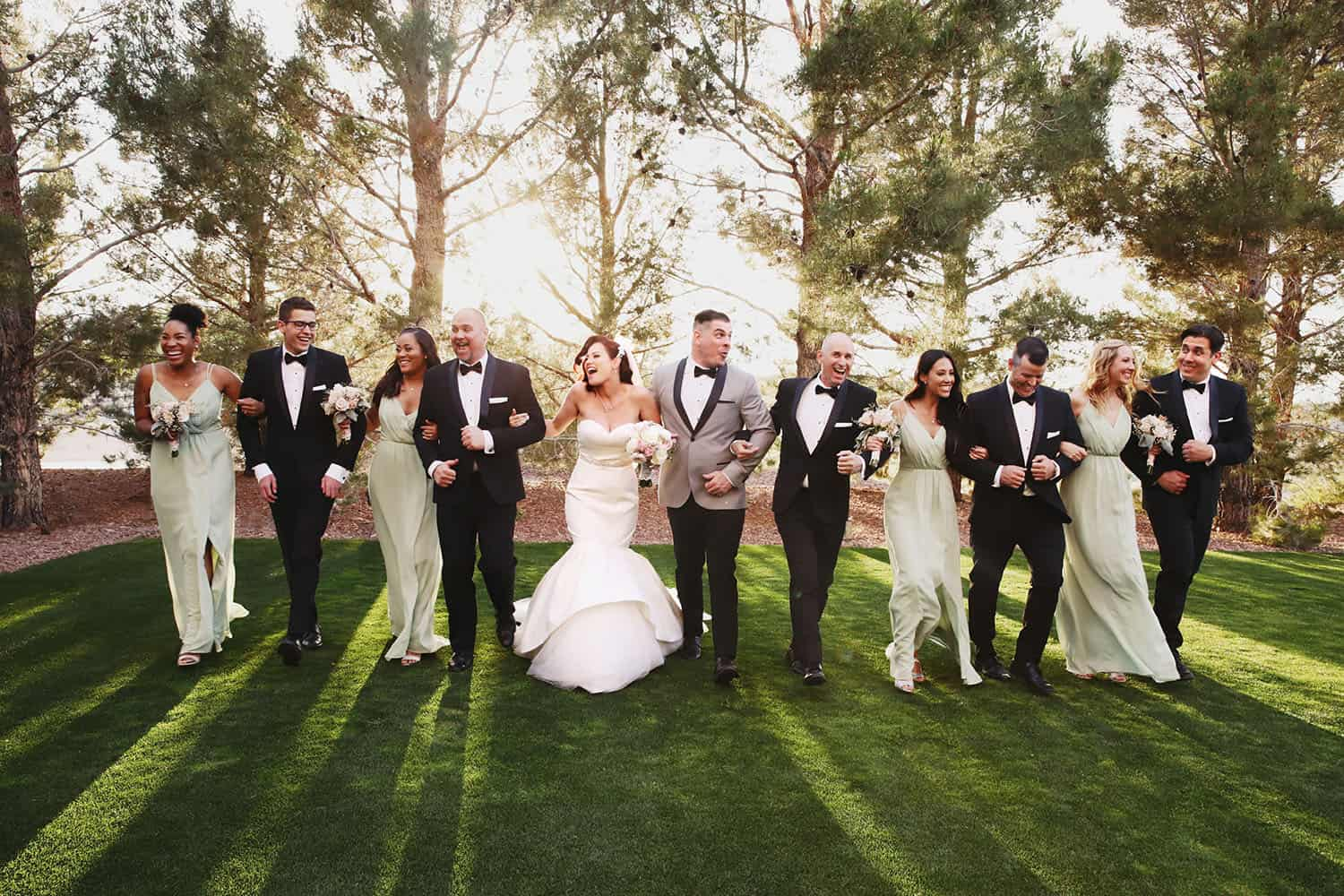 A bride and groom stroll arm-in-arm across a lawn with their bridesmaids and groomsmen.