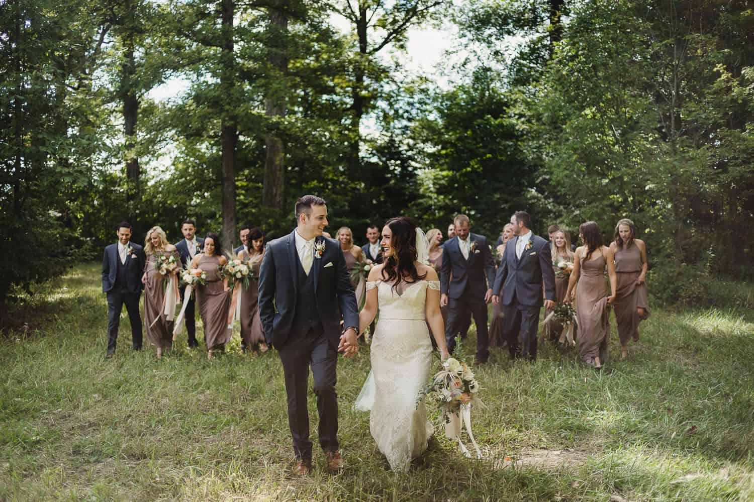 A bride and groom lead the way across a field with their wedding party.