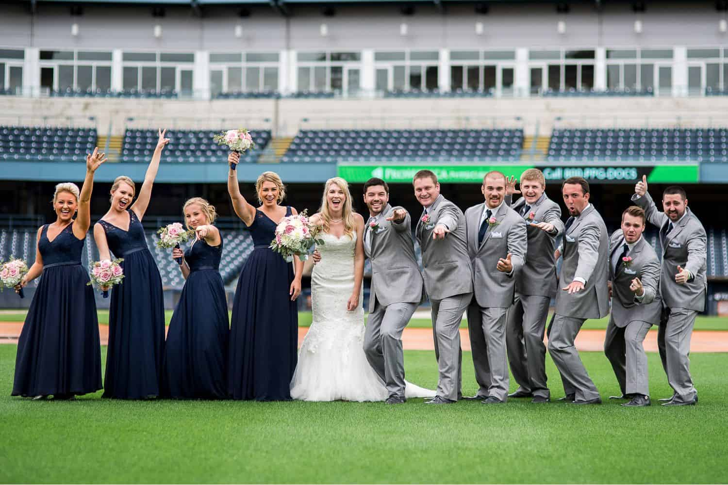 A wedding party strikes a pose on a baseball field.