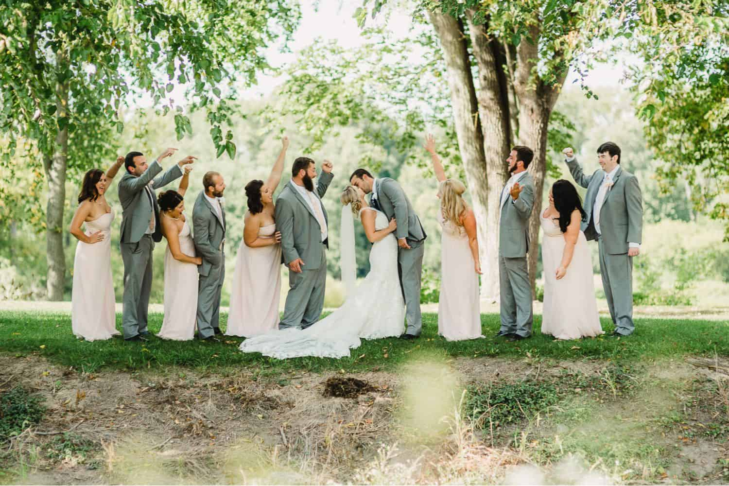 A wedding party poses with the bride and groom in the middle of their line-up kissing.
