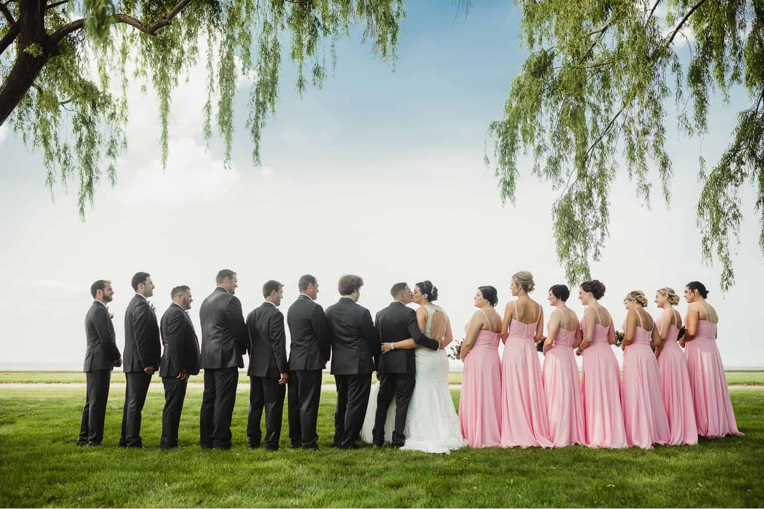 A wedding party stands beneath a willow tree with their backs to the camera as the bride and groom kiss in the middle.