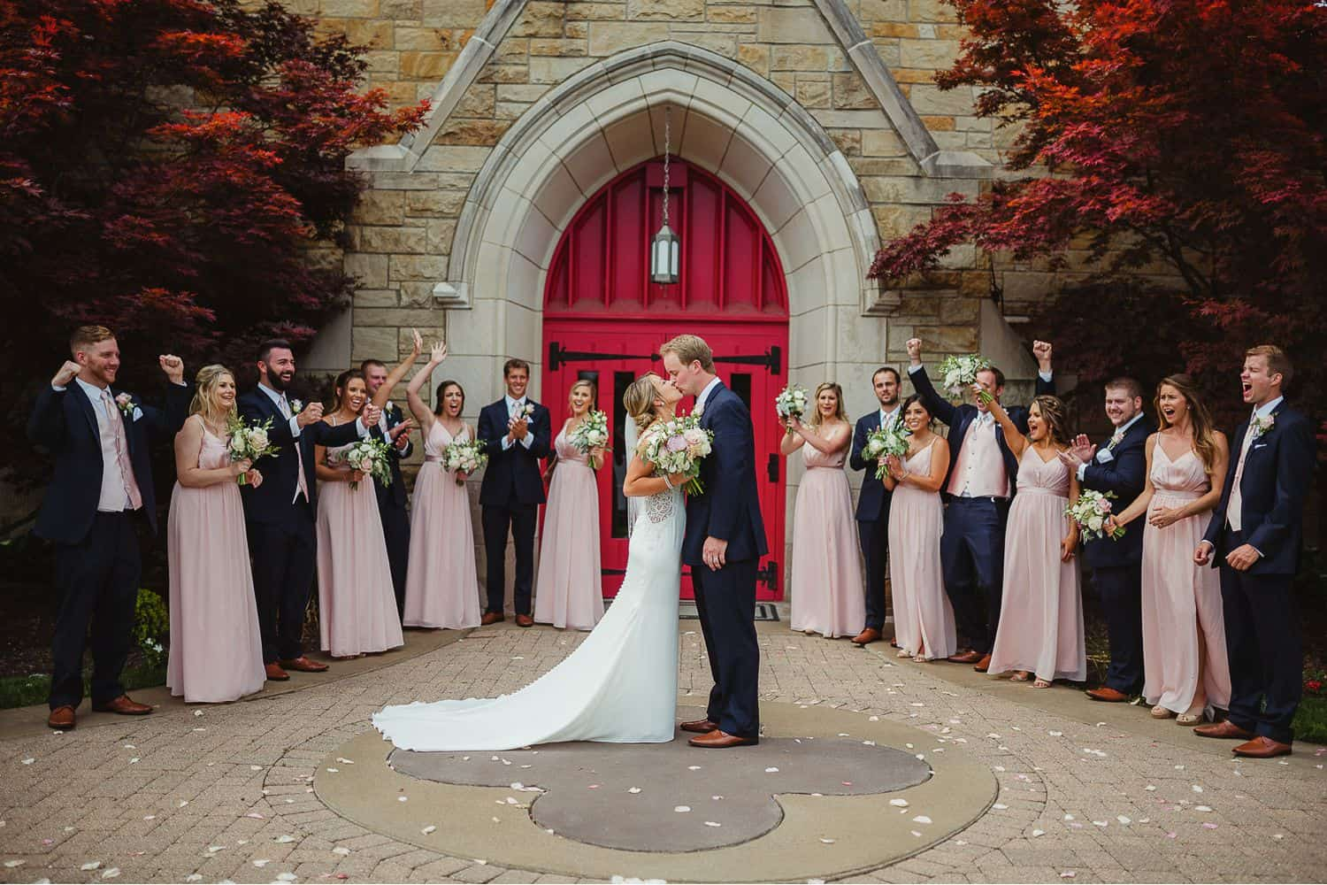 A bride and groom kiss at the center of a circle of bridesmaids and groomsmen.