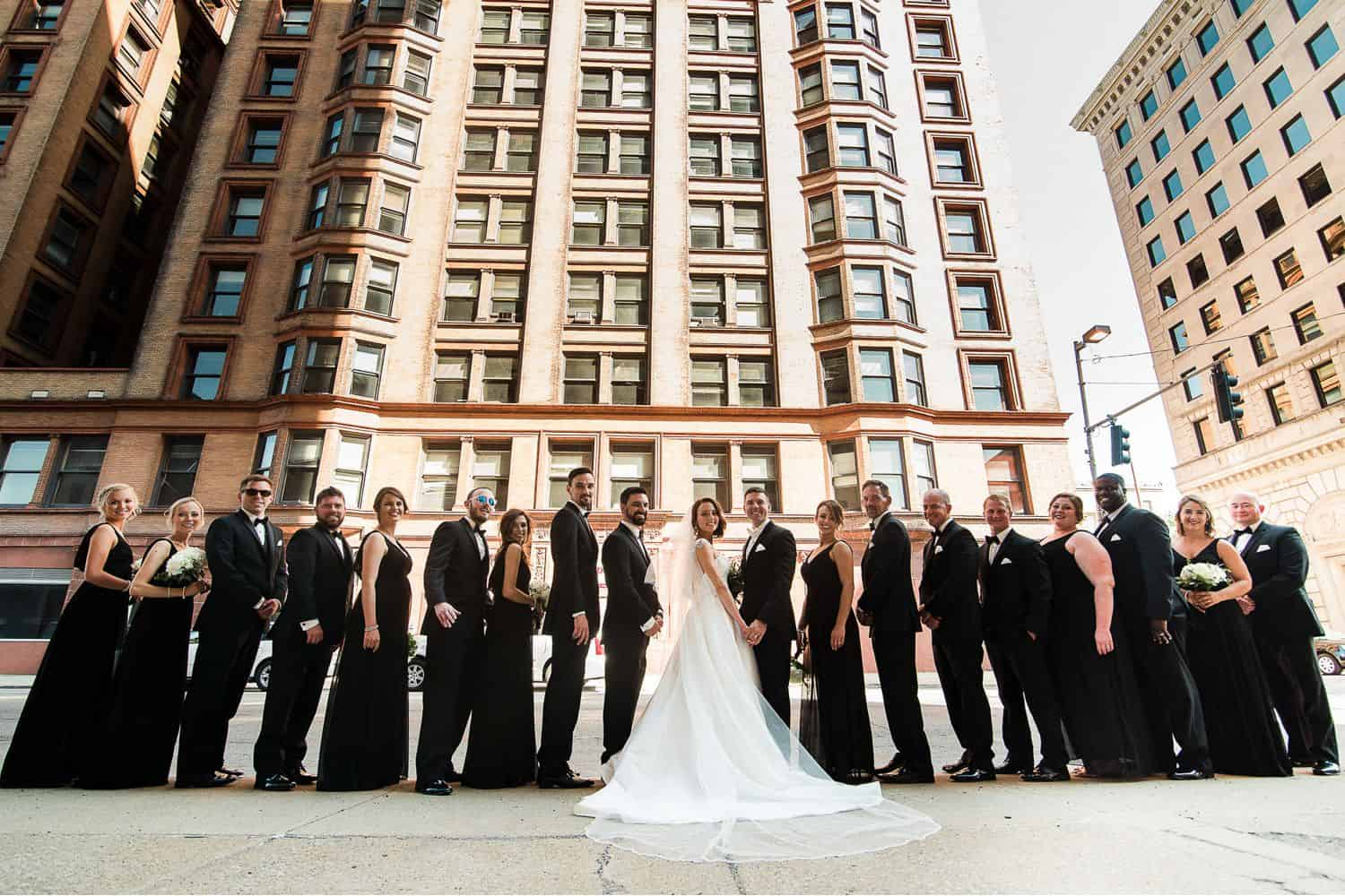A bride and groom stand shoulder-to-shoulder with their wedding party in the middle of a city.
