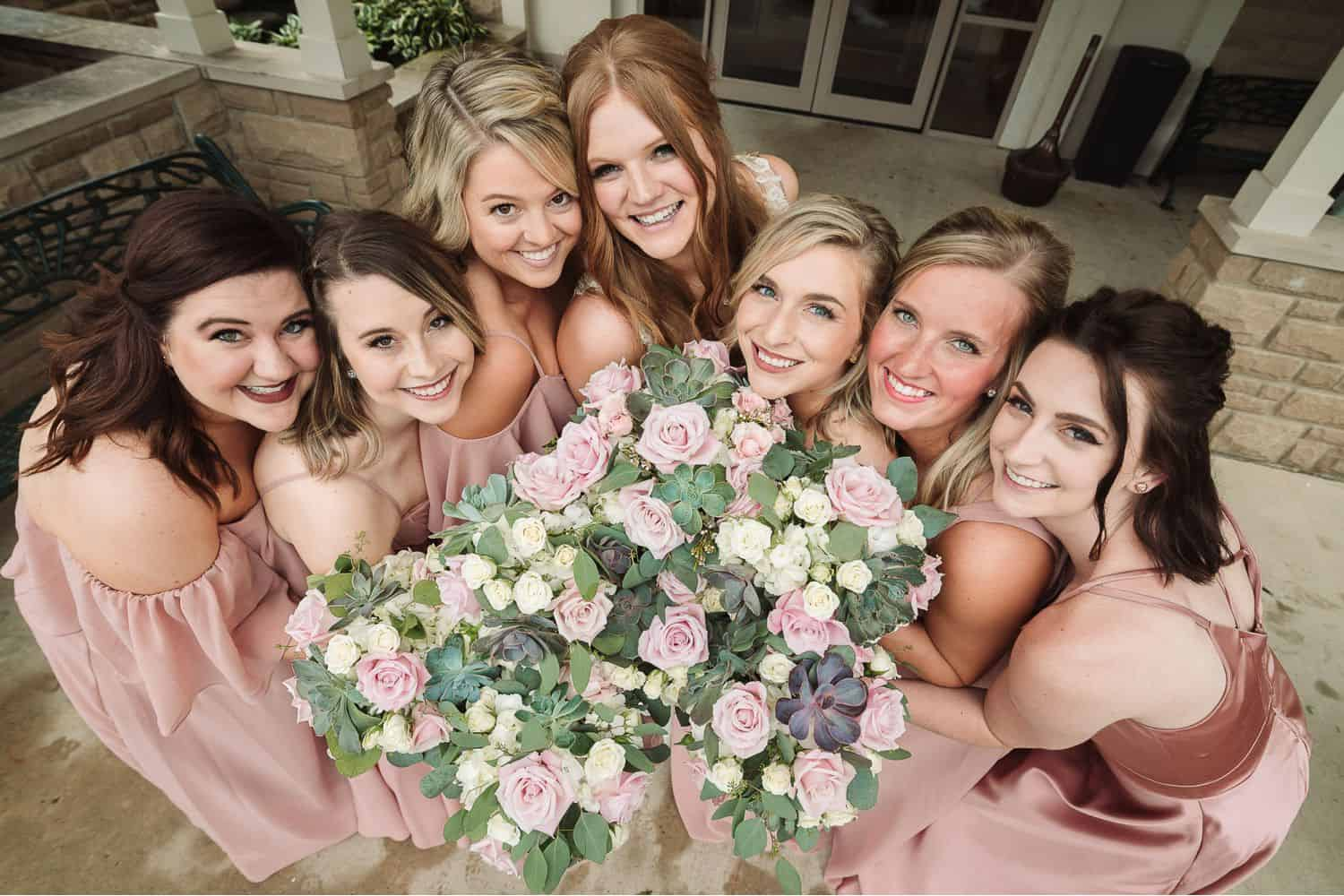 Bridesmaids in pink dresses surround a collection of pastel bouquets.