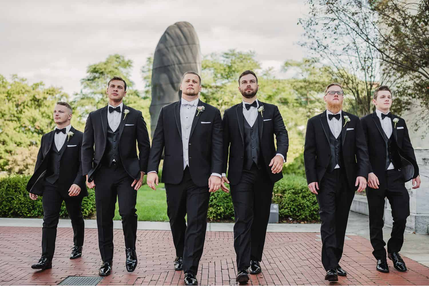 A row of groomsmen in black suits walk across a brick courtyard.