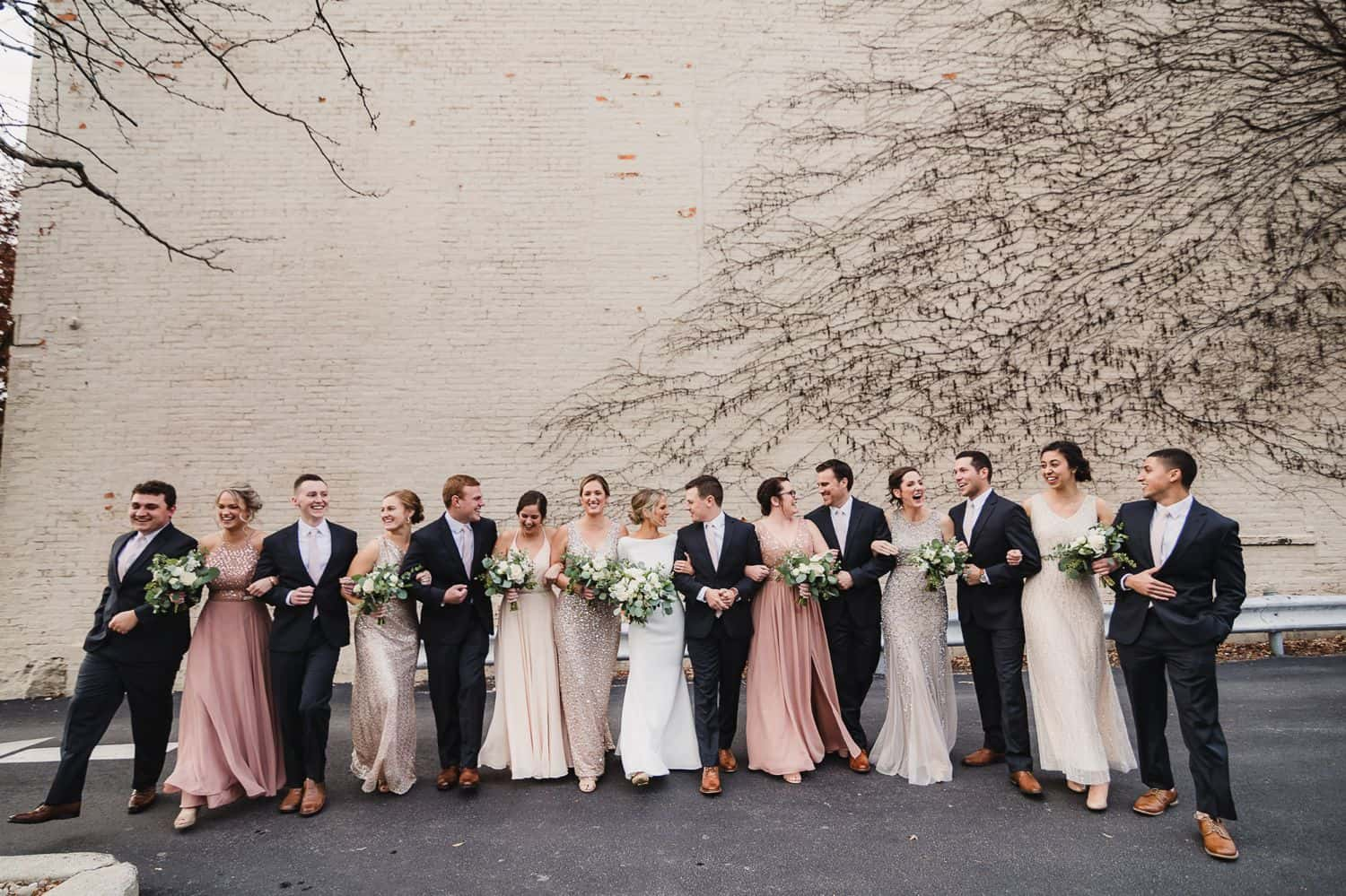 A wedding party in colorful dresses and black tuxes poses in front of a vine-covered wall.