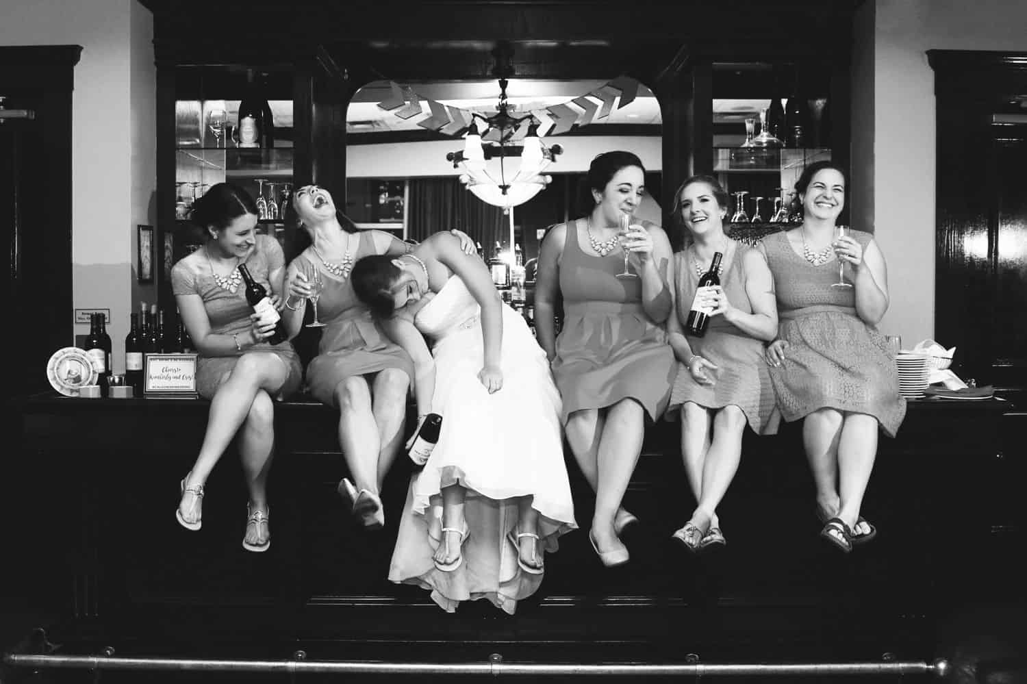 A bride and her bridesmaids sit on a bar with beers in their hands.
