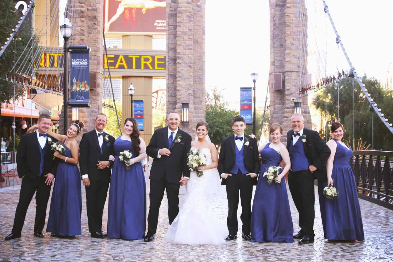 A wedding party wearing navy and black pose on the streets of Las Vegas.