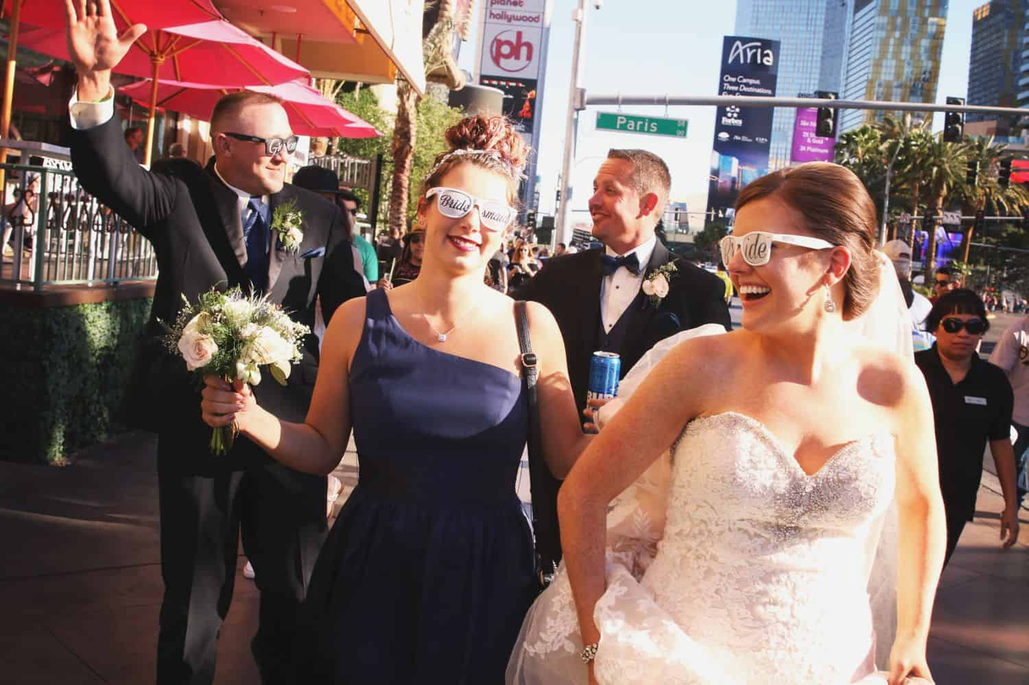 A wedding party walks through Las Vegas wearing sunglasses.