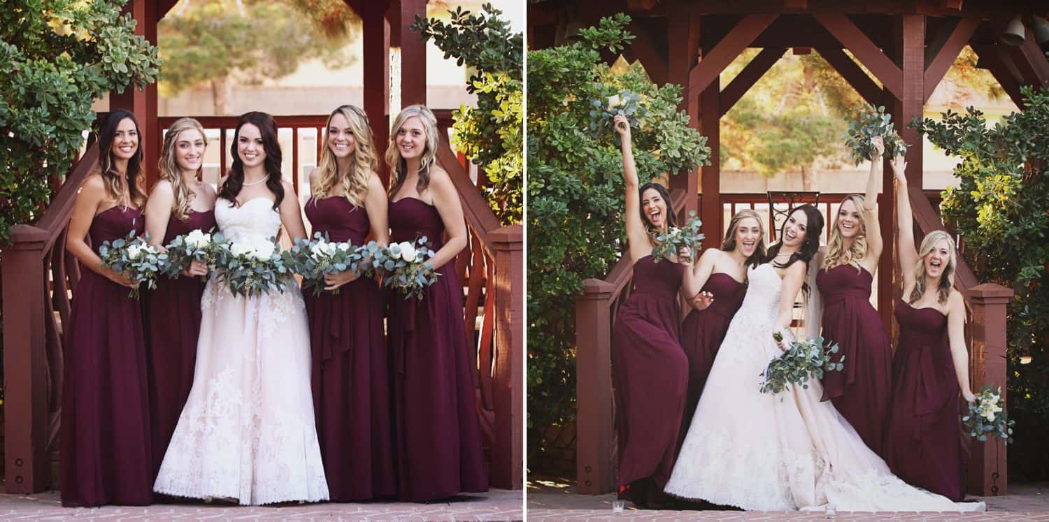 Bridesmaids wearing fall colors pose with the bride beneath a natural wooden arbor.