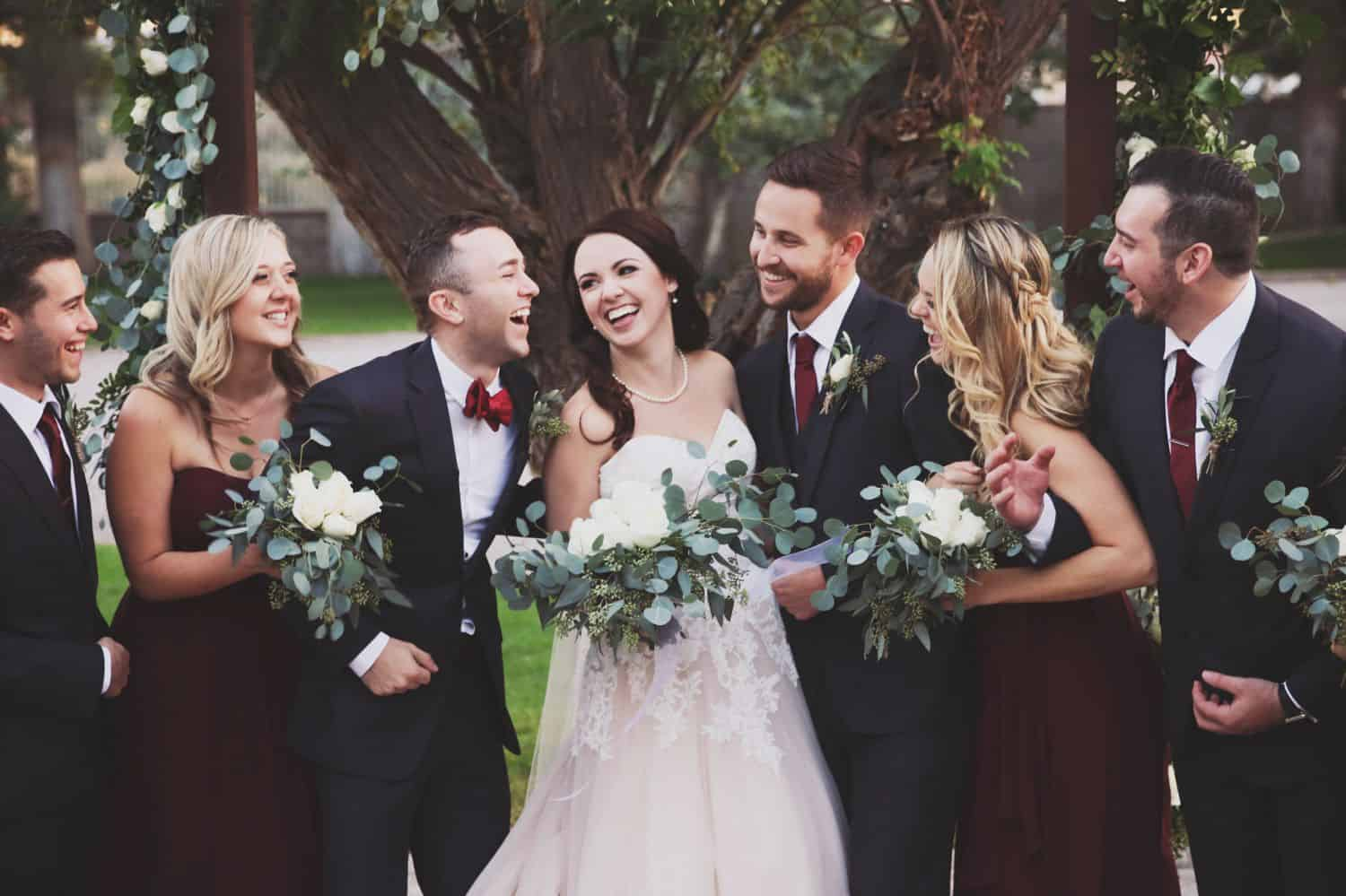 A wedding party stands shoulder-to-shoulder laughing expressively.