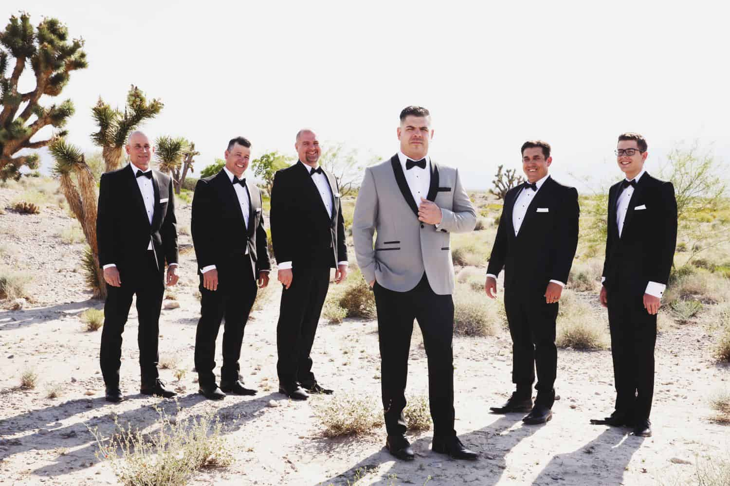 A groom in a grey tuxedo stands slightly in front of his groomsmen.