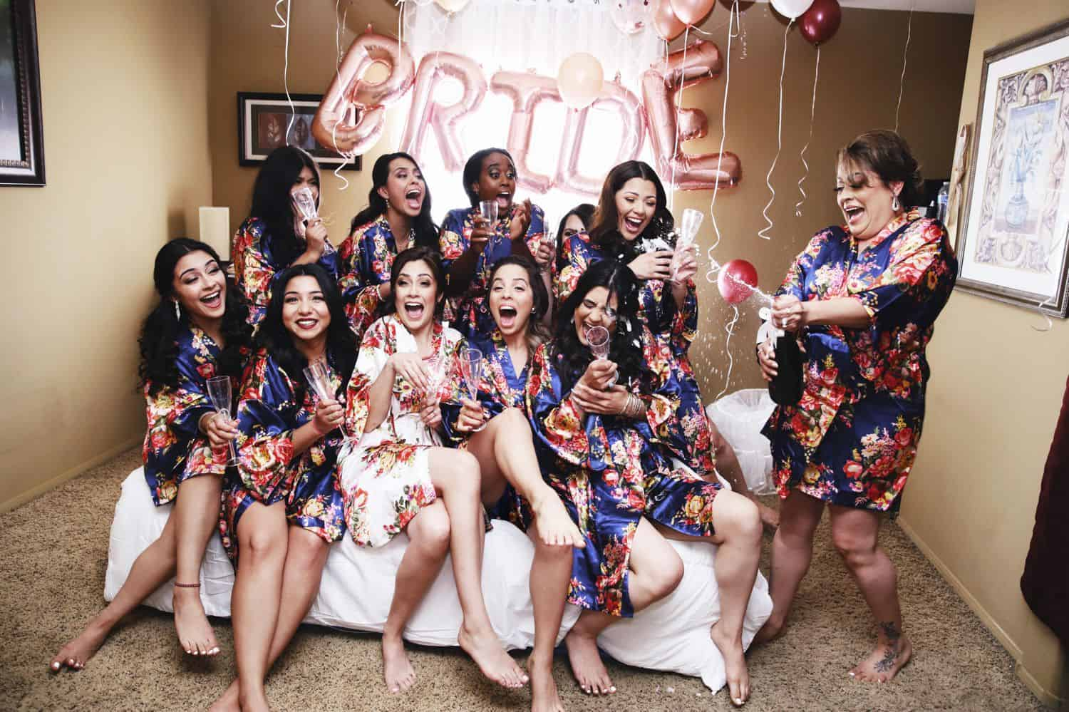 A group of bridesmaids shrieks as a champagne bottle explodes on them.