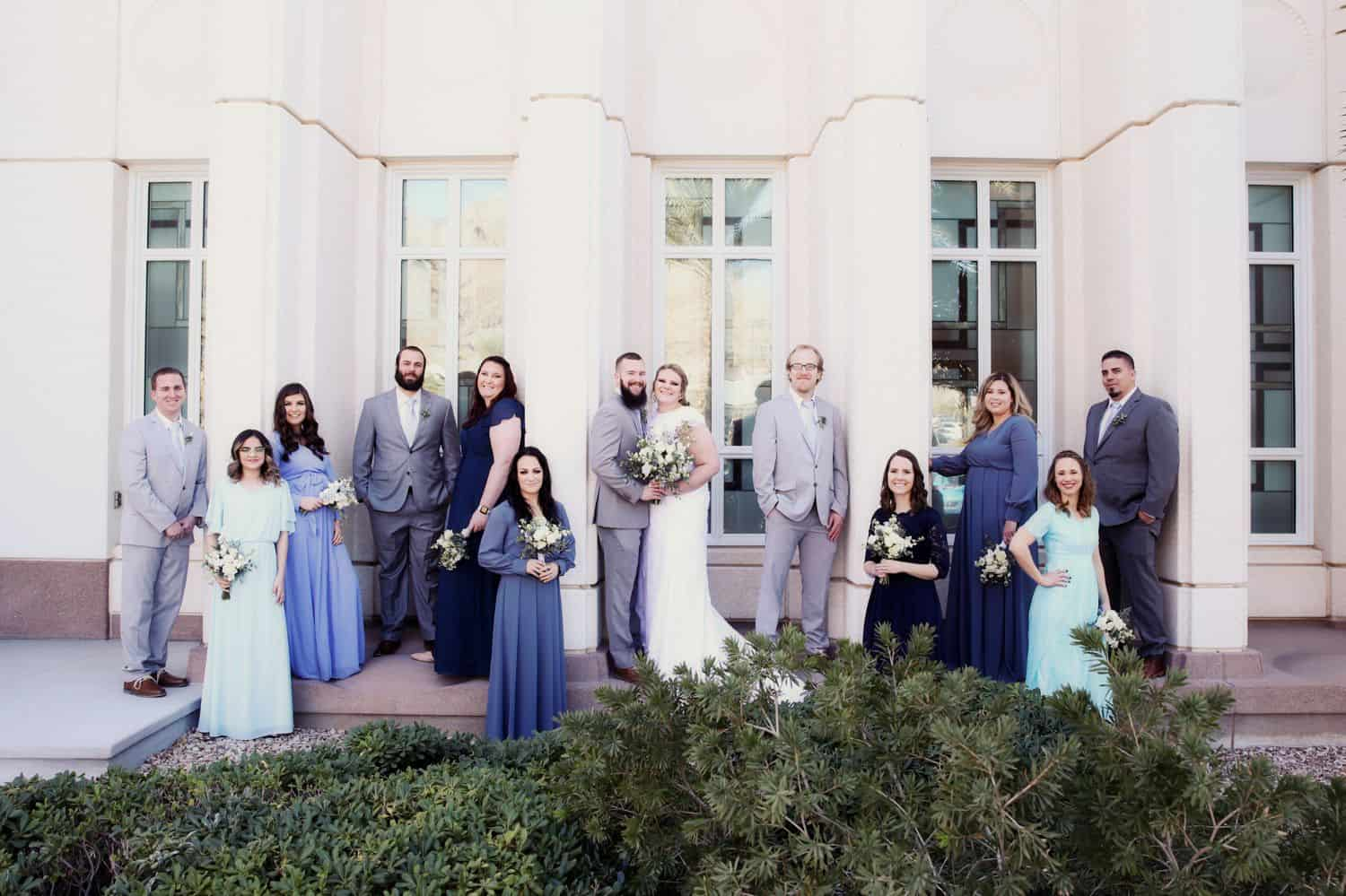 A blue and grey-dressed wedding party stands on the front porch of an antebellum mansion.