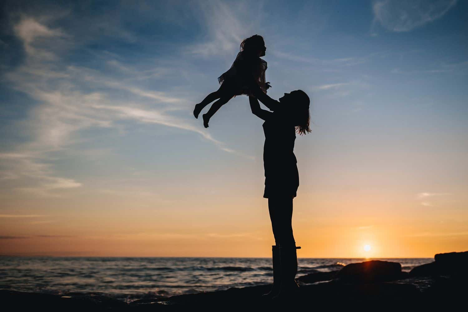 A silhouette of a woman as she lifts her child into the air at sunset on a beach.