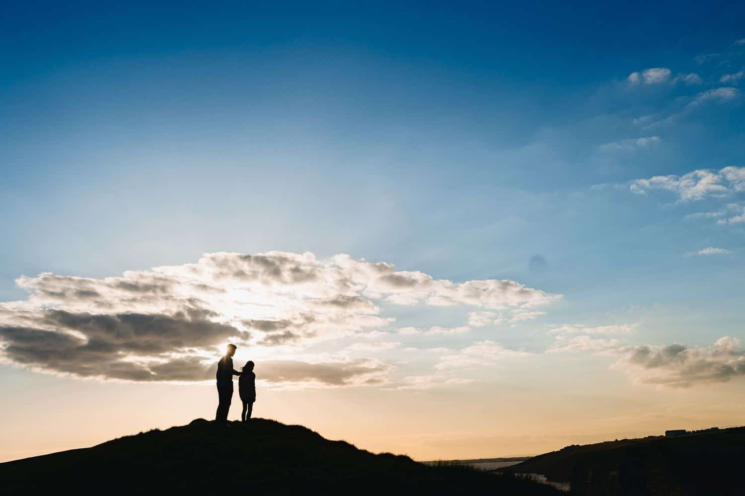 Silhouette of a father standing with his hand on his child's shoulder. They are standing on a hill overlooking the sunset sky.