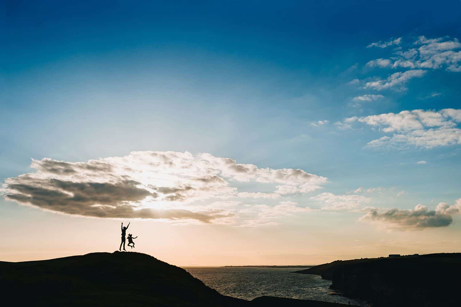Silhouette of a parent and a child jumping on a hill overlooking the ocean.