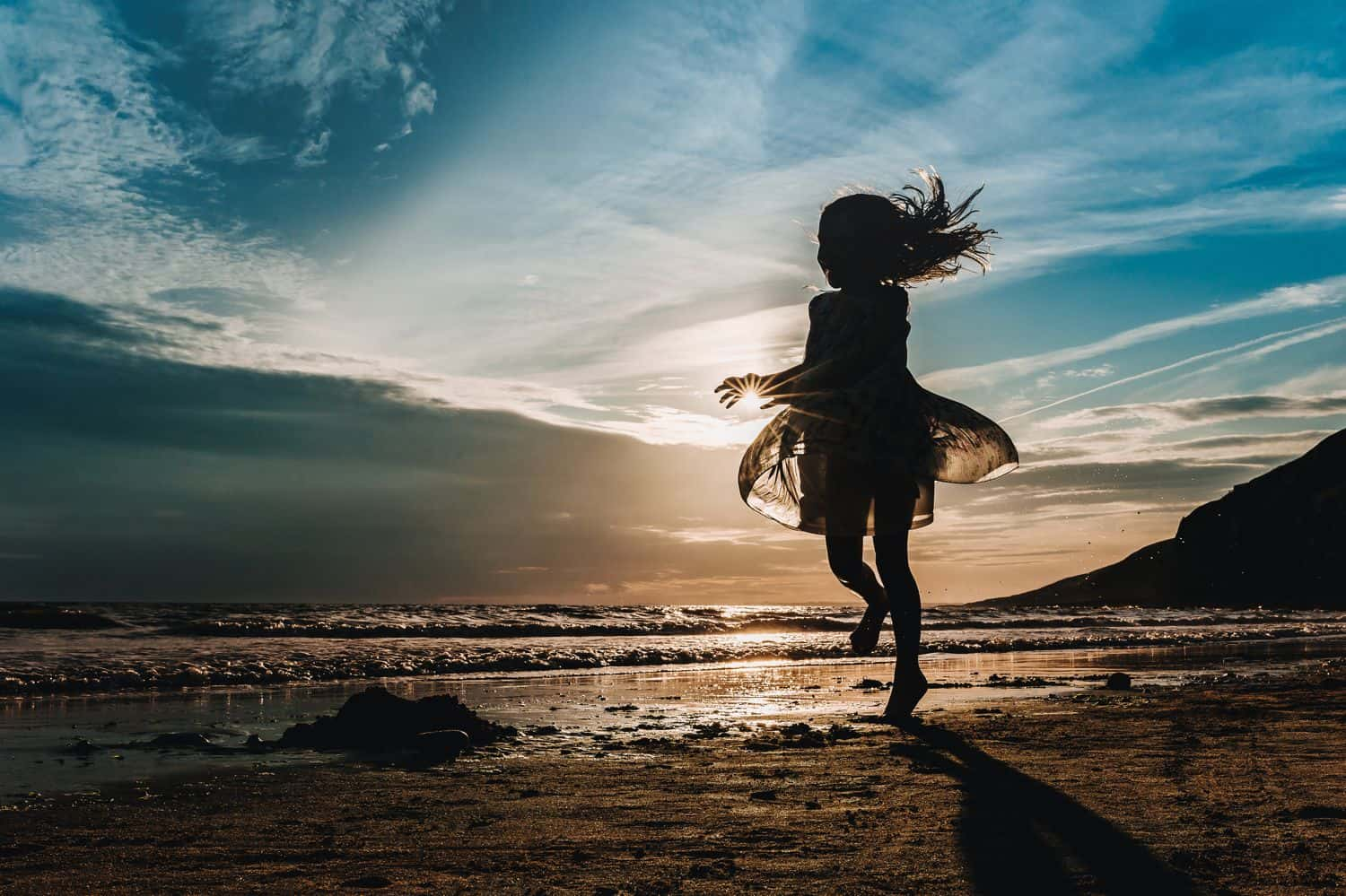 Silhouette of a little girl in a flowing dress running along the beach at sunset.