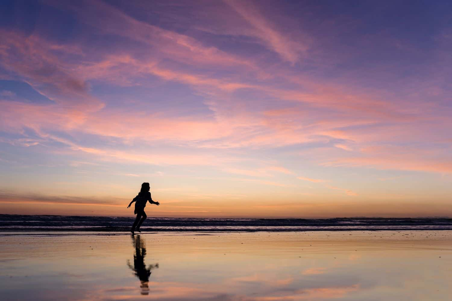 Silhouette of a child reflected in the low tide of a beach at sunset.