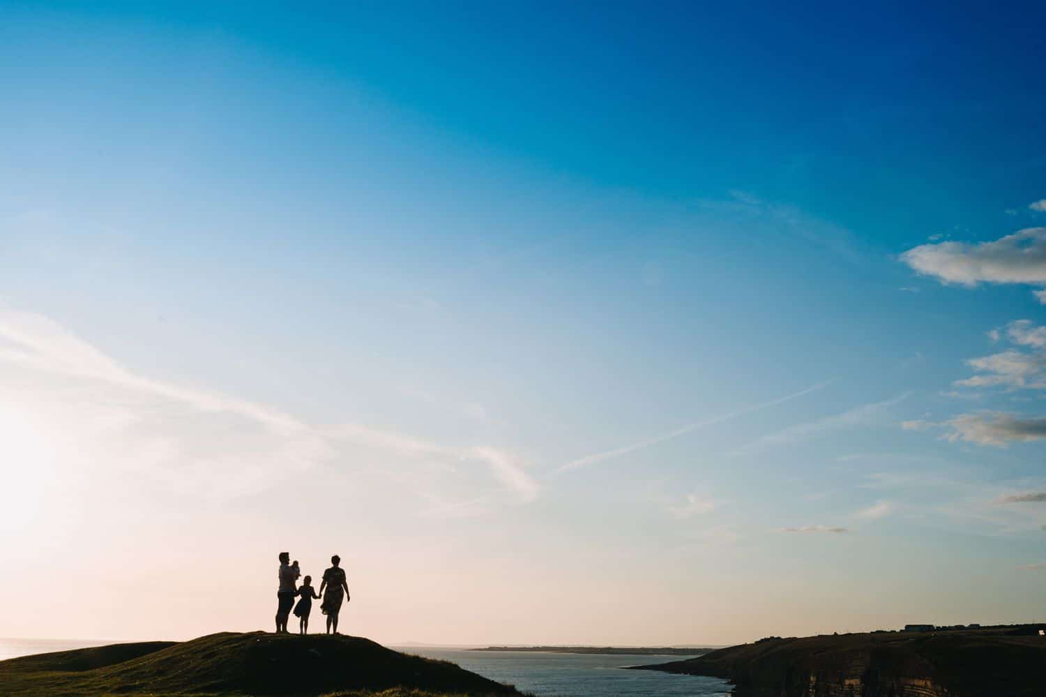 Silhouette of a family standing on a hill overlooking the ocean.