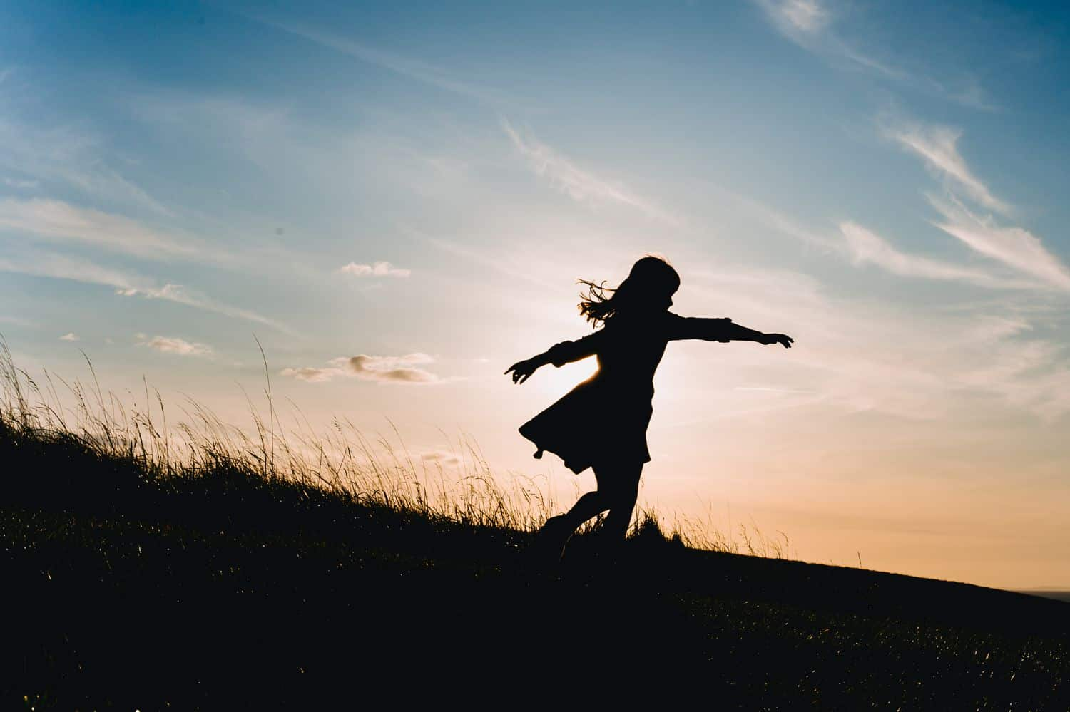 Silhouette of a little girl in a twirly dress running down a grassy hill at sunset.