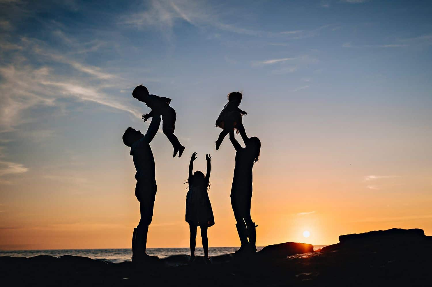 Silhouette of two parents lifting their children into the sky overlooking a beach at sunset. A third child stands in between them with her arms lifted.