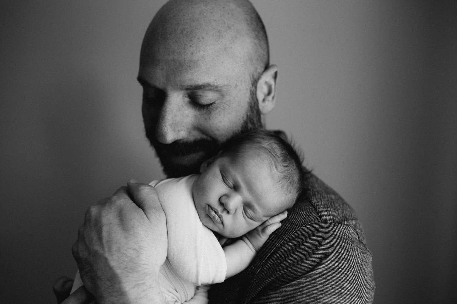 Black and white photo of a father holding his newborn baby close to his cheek.