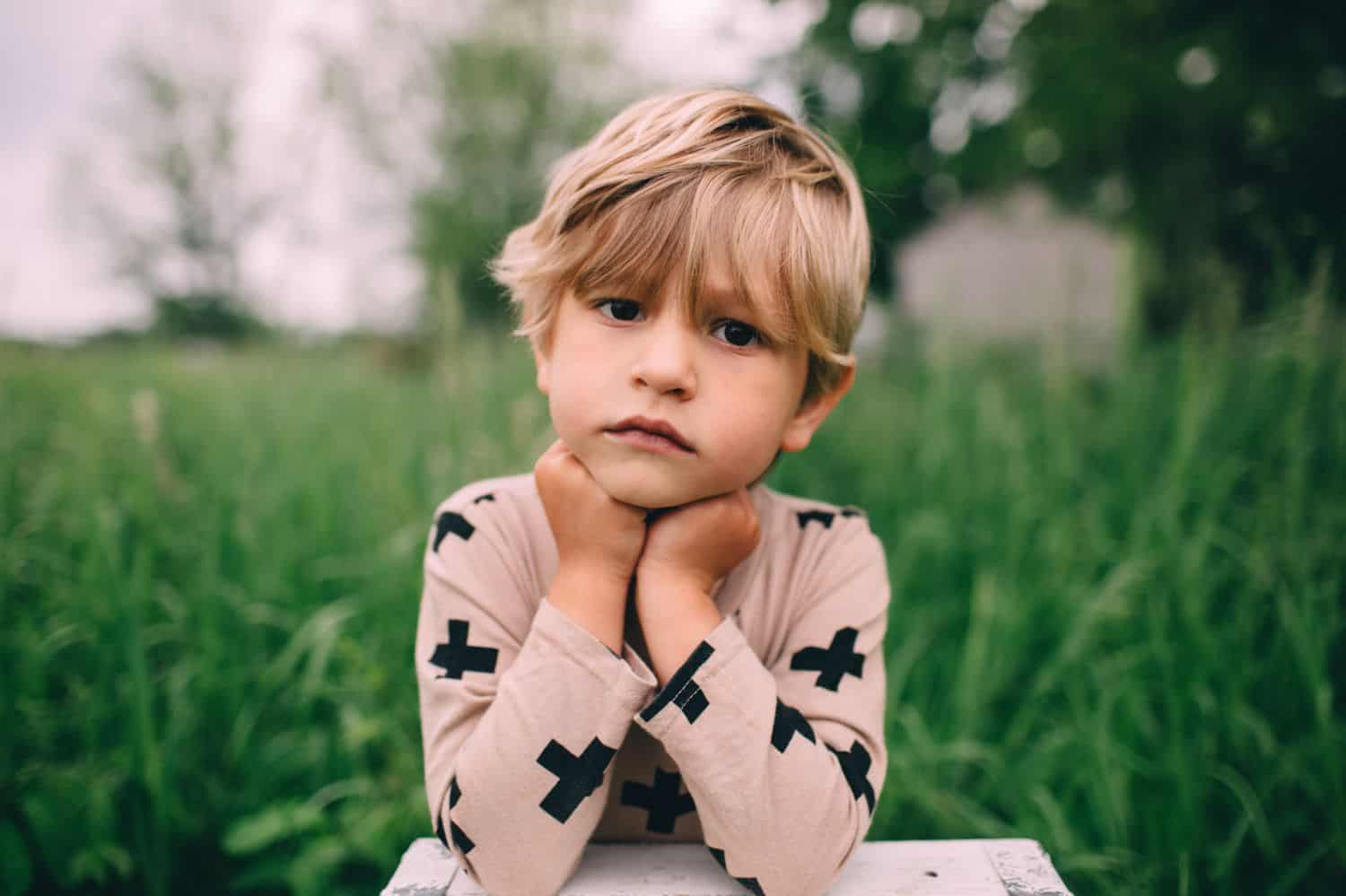 A serious looking child sits in a grassy field with their chin in their hands.