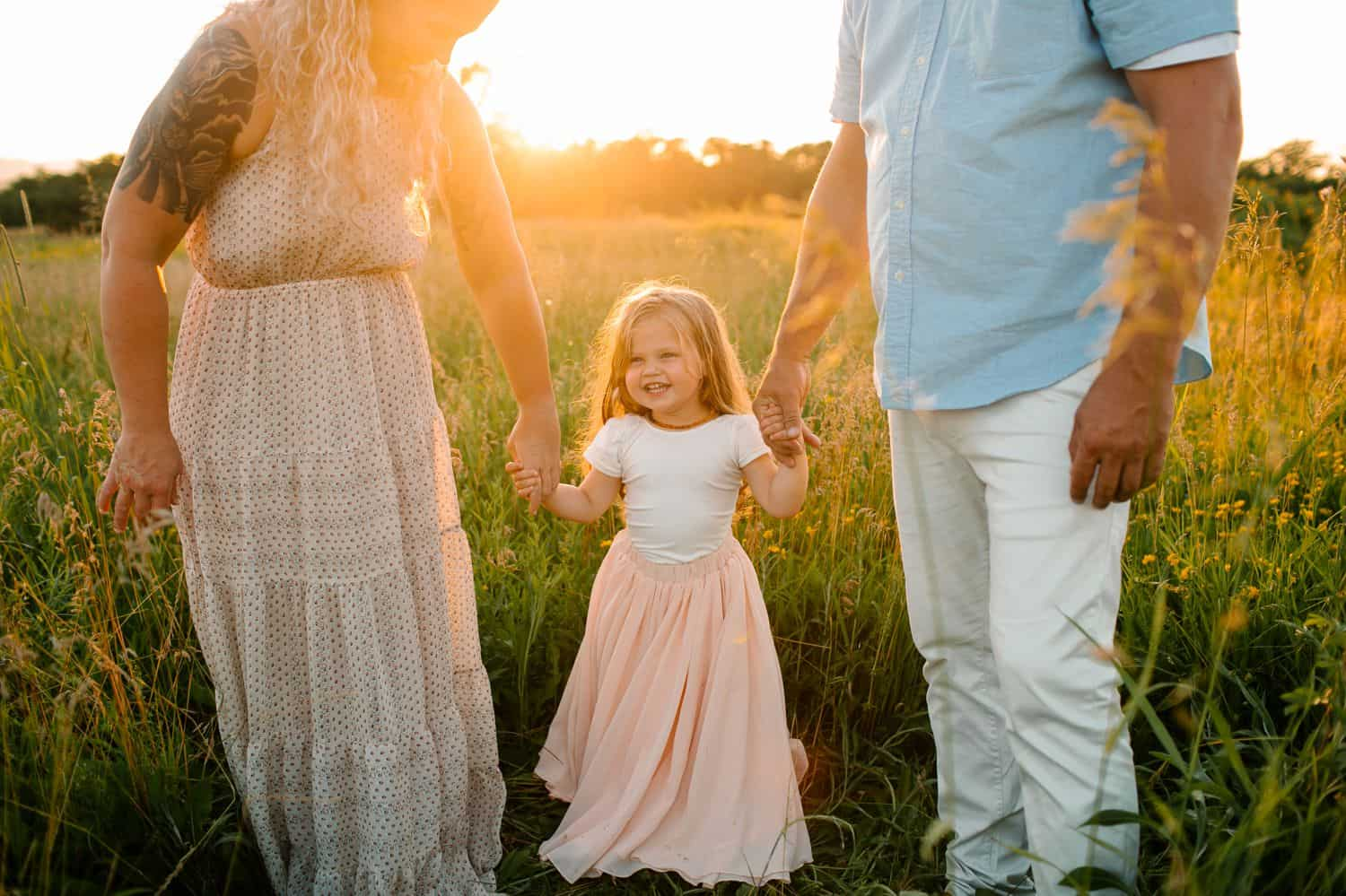 A little girl in a pink skirt holds her parents hands in a field at sunset.