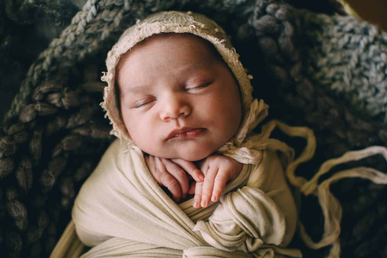 A newborn baby sleeps swaddled in linen blankets.
