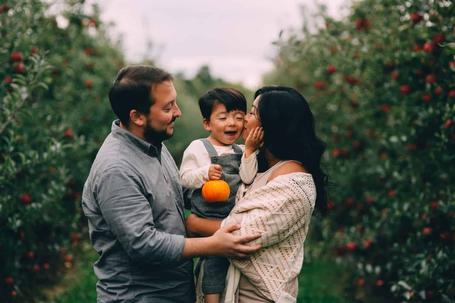 A little boy in overalls is hugged between his parents in the middle of an orchard.