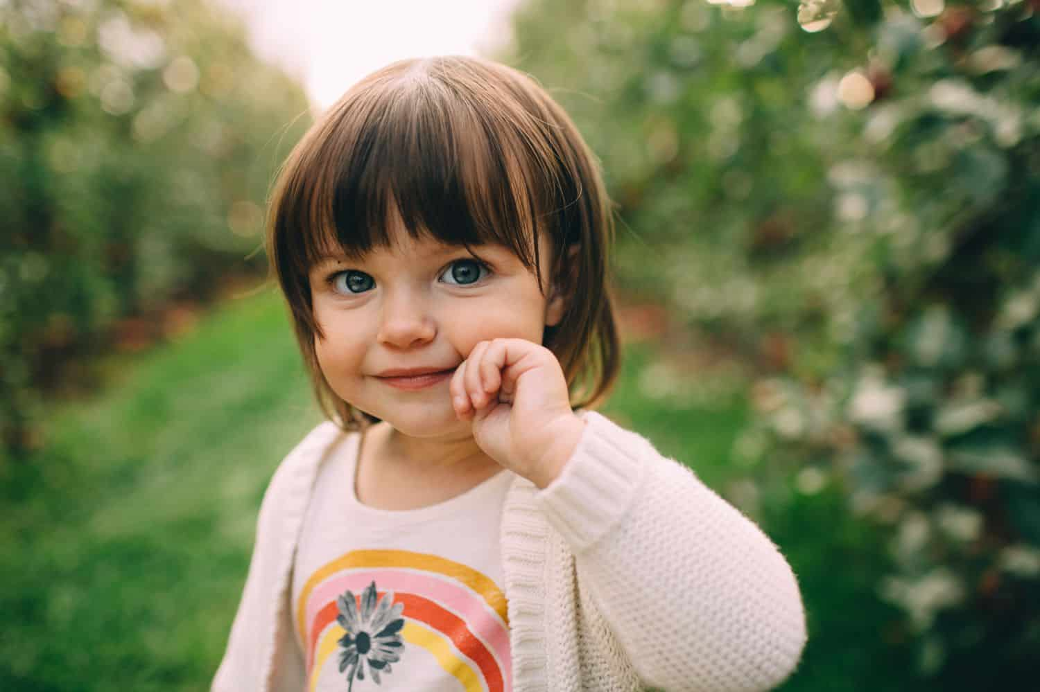 A little girl wearing a rainbow t-shirt stands in an apple orchard.