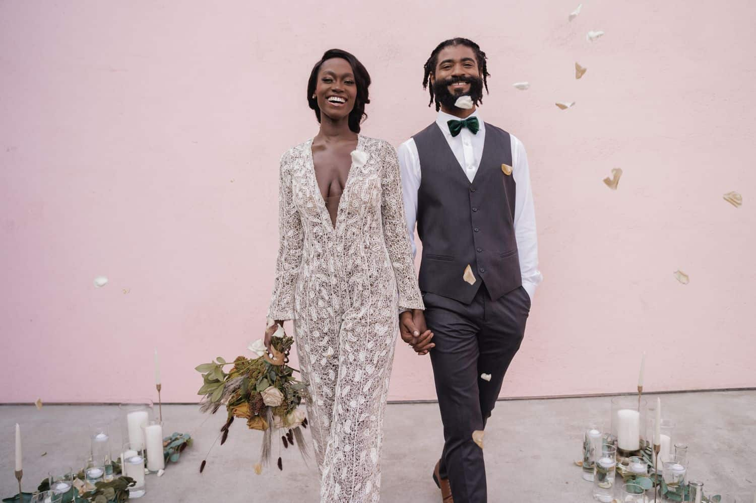 A bride in lace jumpsuit walks in front of a pink wall with her groom who is wearing a gray suit. They are in a shower of flower petals.
