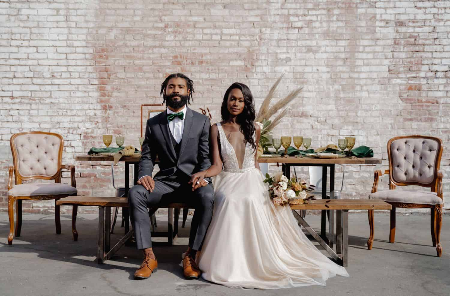 A Black bride and groom sit on a decorated picnic table wearing a gray tuxedo and an ivory wedding gown in front of a brick wall.