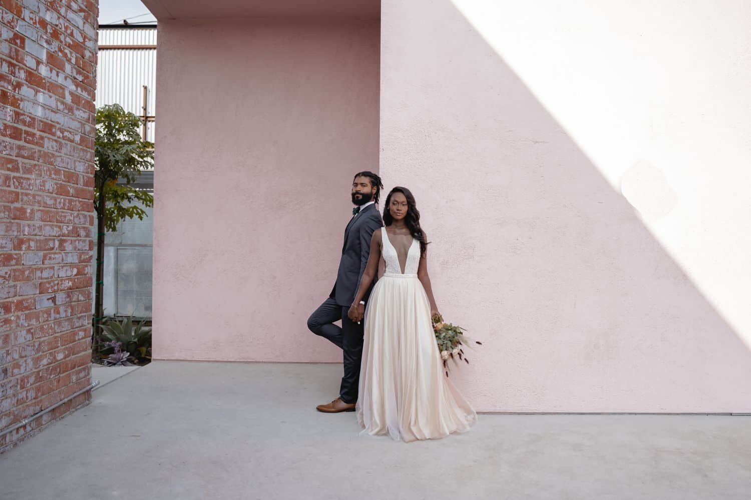 A Black bride and groom stand at the corner of a pink building beneath a slant of light.